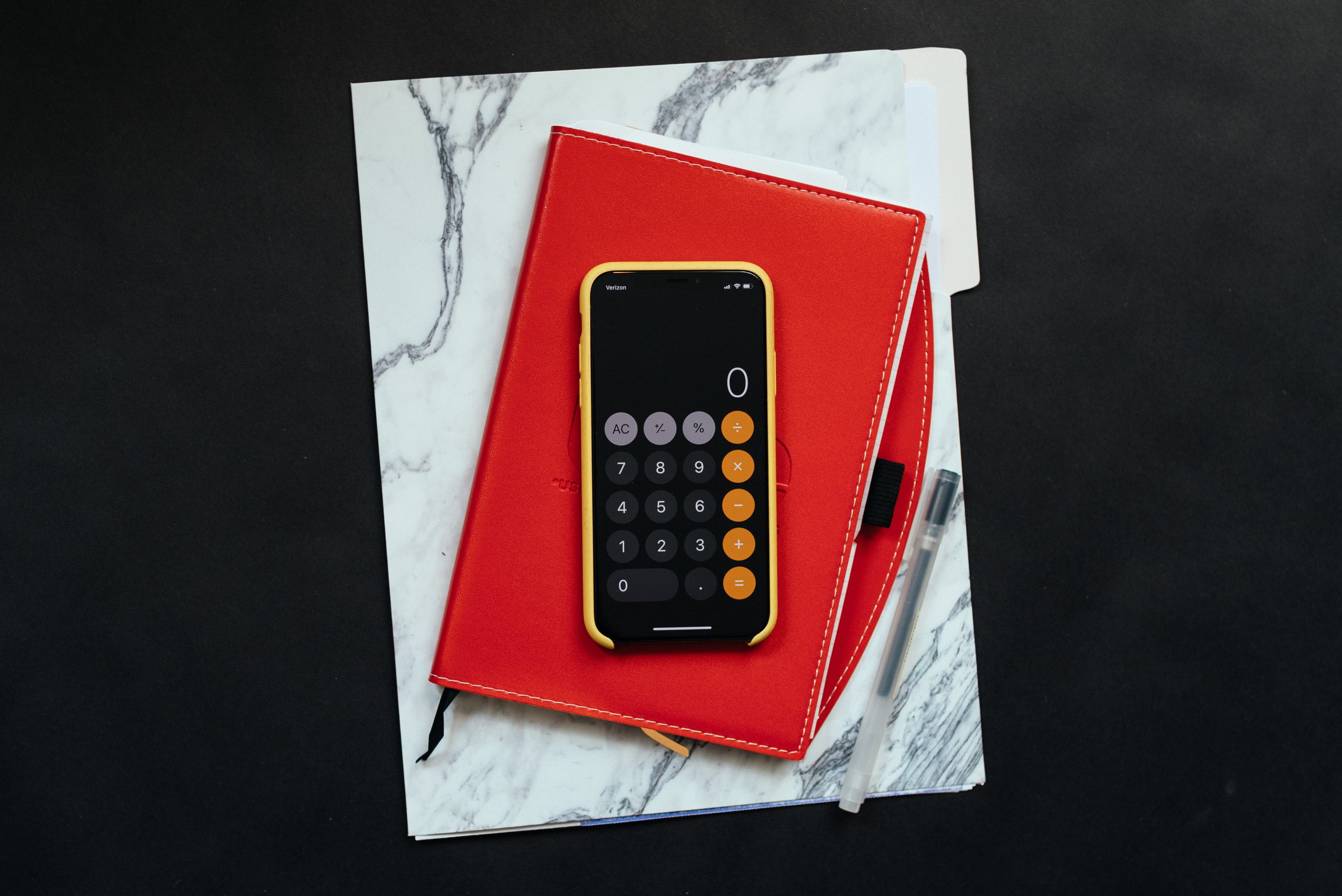 Calculator On Red And Marbled Folder