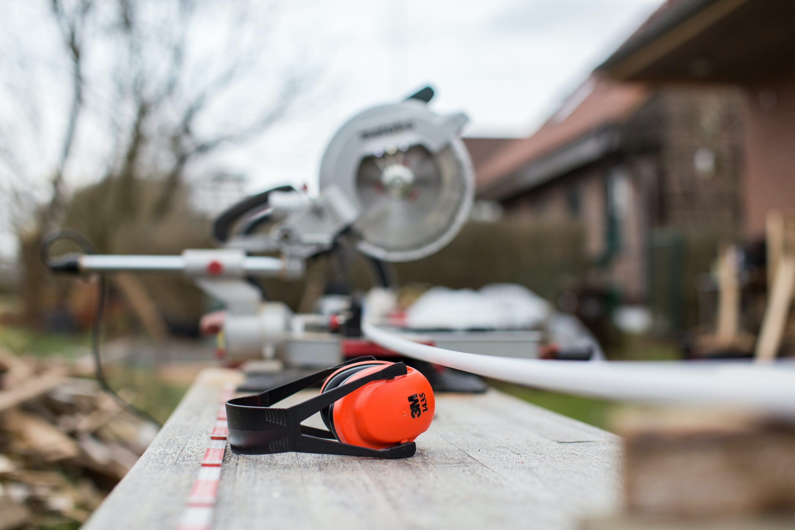 orange noice cancelling headphones sitting on a piece of wood next to a circular saw outside a home